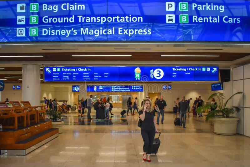 Hoogste mening van Zakeis, Etikettering en Controle blauwe tekens en vrouw die met bagage in Orlando International Airport lopen royalty-vrije stock fotografie