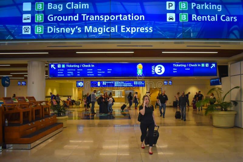 Hoogste mening van Zakeis, Etikettering en Controle blauwe tekens en vrouw die met bagage in Orlando International Airport lopen royalty-vrije stock afbeeldingen