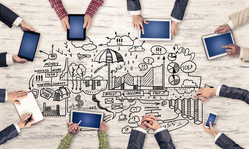 Hoogste mening van zakenlui die bij lijst zitten en gadgets gebruiken royalty-vrije stock fotografie