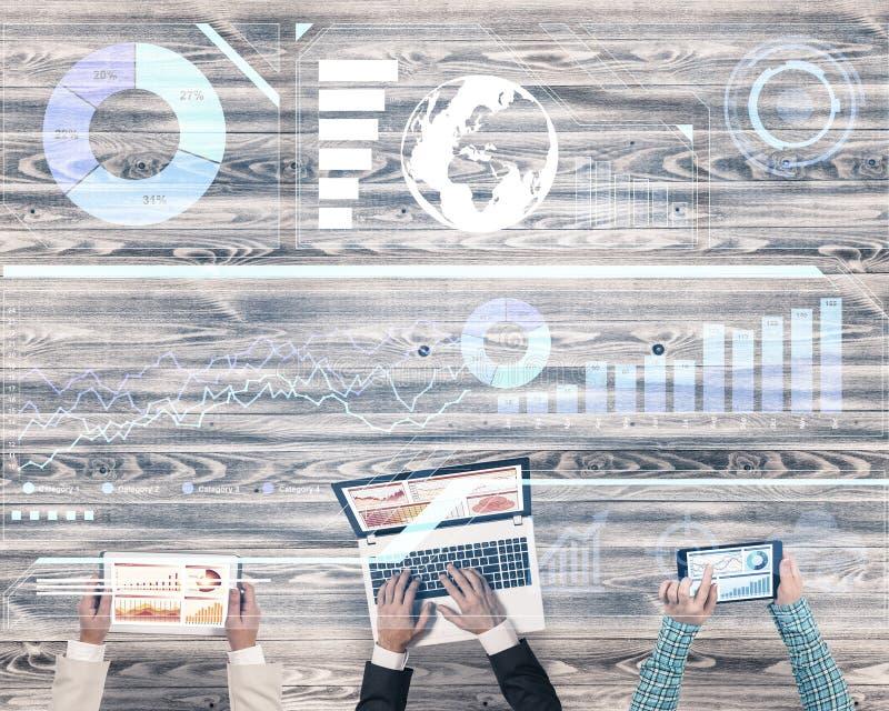 Hoogste mening van zakenlui die bij lijst zitten en gadgets gebruiken stock foto's