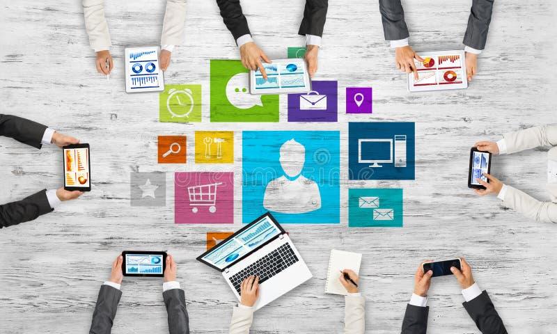 Hoogste mening van zakenlui die bij lijst zitten en gadgets gebruiken stock foto