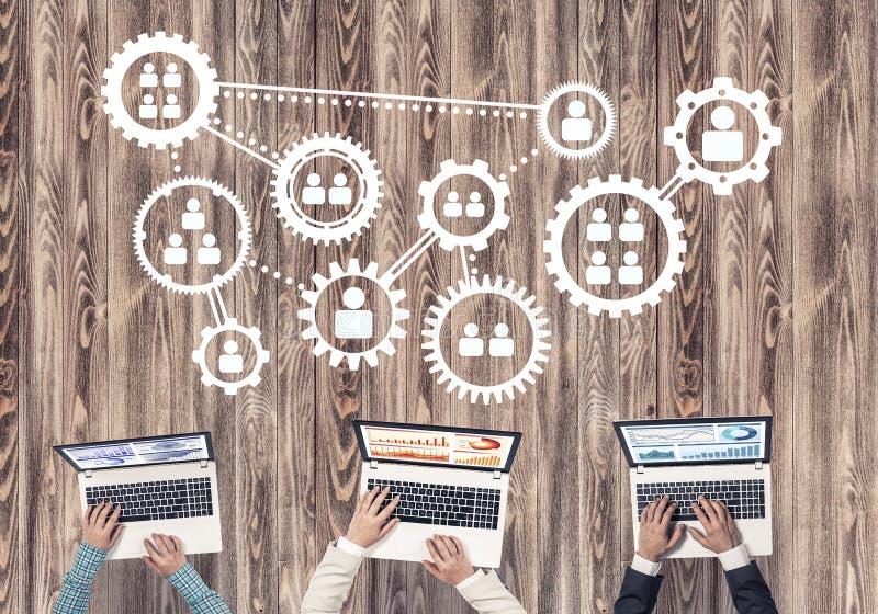 Hoogste mening van zakenlui die bij lijst zitten en gadgets gebruiken royalty-vrije stock afbeelding