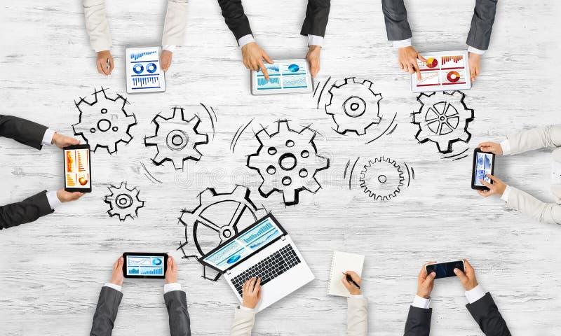 Hoogste mening van zakenlui die bij lijst zitten en gadgets gebruiken stock afbeeldingen