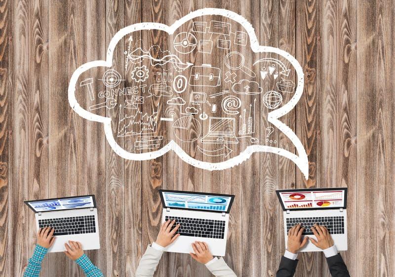 Hoogste mening van zakenlui die bij lijst zitten en gadgets gebruiken stock afbeelding