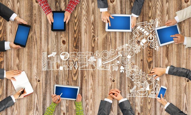 Hoogste mening van zakenlui die bij lijst zitten en gadgets gebruiken royalty-vrije stock foto's