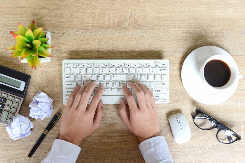Hoogste mening van zakenman die aan laptop, hij zitting bij zijn het werk het werkruimte werken met kopkoffie stock foto's