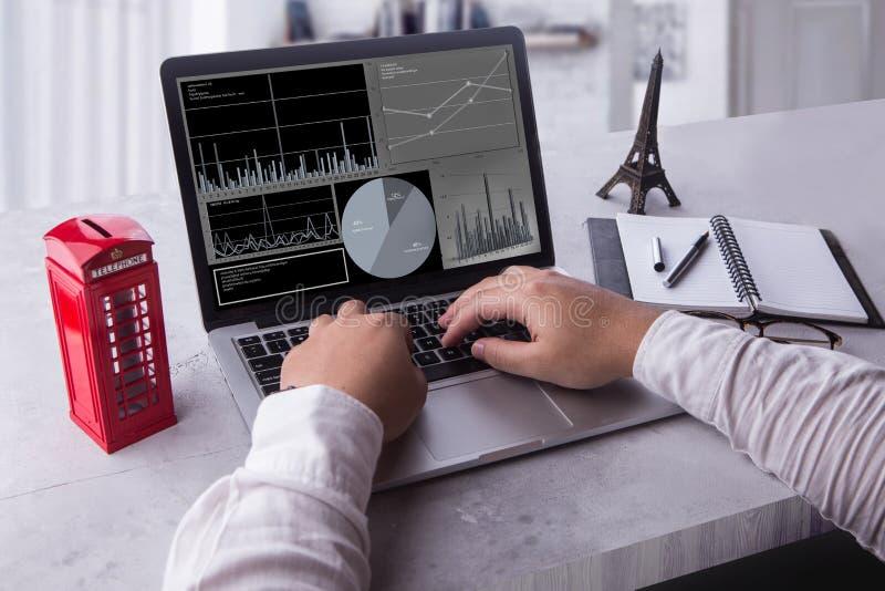 Hoogste mening van zakenman die laptop computer met statistiekengegevens met behulp van over het scherm royalty-vrije stock foto's