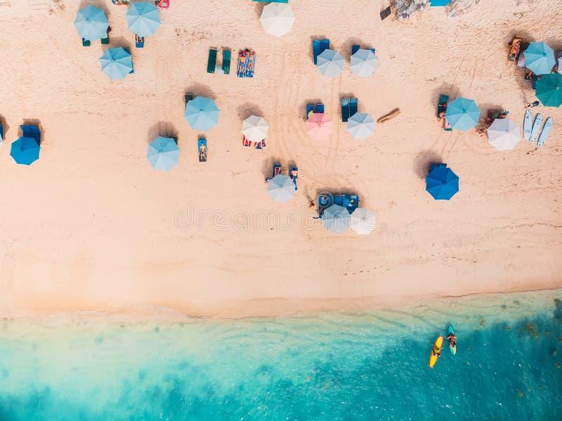 Hoogste mening van zandig strand met turkoois zeewater en kleurrijke blauwe paraplu's, luchthommelschot stock afbeeldingen