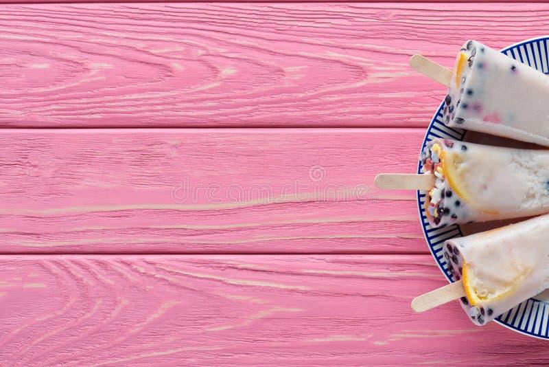 hoogste mening van zoete smakelijke eigengemaakte ijslollys met vruchten en bessen op plaat op roze stock foto