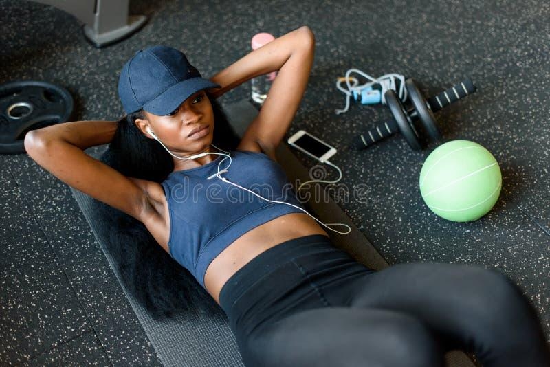 Hoogste mening van zwarte sexy geschiktheidsinstructeur die pers UPS doen bij de gymnastiek en aan muziek in oortelefoons luister royalty-vrije stock afbeeldingen