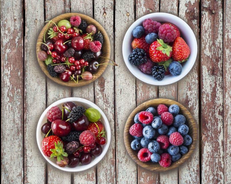 Hoogste mening Vruchten en bessen in kom op een houten achtergrond Rijpe frambozen, bosbessen, kersen, aardbeien, braambessen, royalty-vrije stock afbeelding