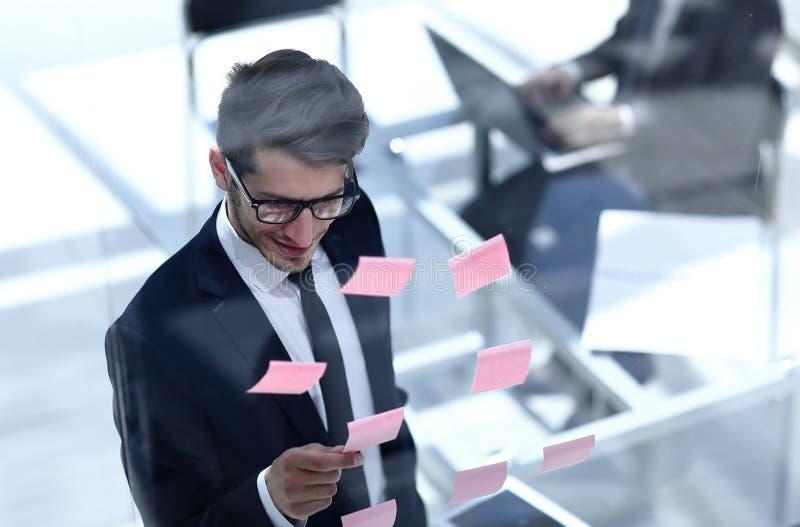 Hoogste mening zakenman die kleverige nota's over het glas lezen stock afbeeldingen