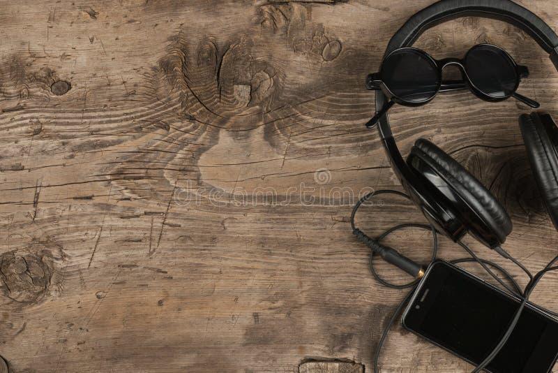 Hoogste mening Zwarte zonnebril, hoofdtelefoons en mobiele telefoon op oud houten bureau, uitstekende achtergrond stock afbeelding