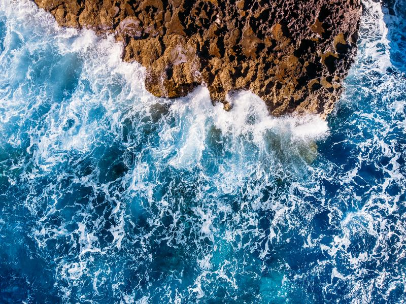 Hoogste menings Azuurblauwe blauwe overzees met golven die op strand en rotsen slaan Lucht Foto royalty-vrije stock afbeelding