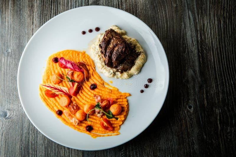Hoogste menings groot smakelijk stuk van goed uitgevoerd geroosterd vleeslapje vlees op aardappelpuree stock afbeelding