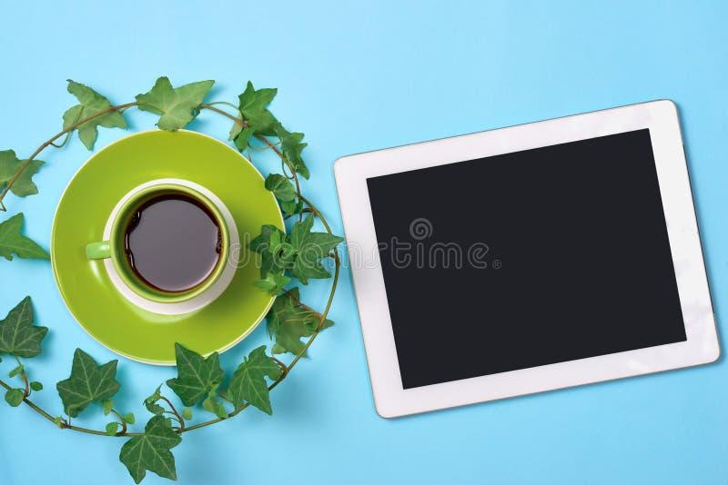 Hoogste menings hete koffie in groene kop en digitale tablet met bladeren royalty-vrije stock fotografie