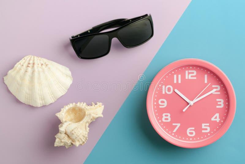 Hoogste menings roze wekker en zonnebril en shells op een kleurrijke achtergrond, zoals een tijd op zee stock afbeeldingen