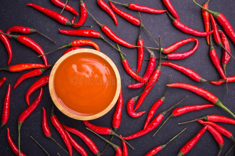 Hoogste menings verse roodgloeiende Spaanse peper met saus in houten kom op zwarte stock afbeeldingen
