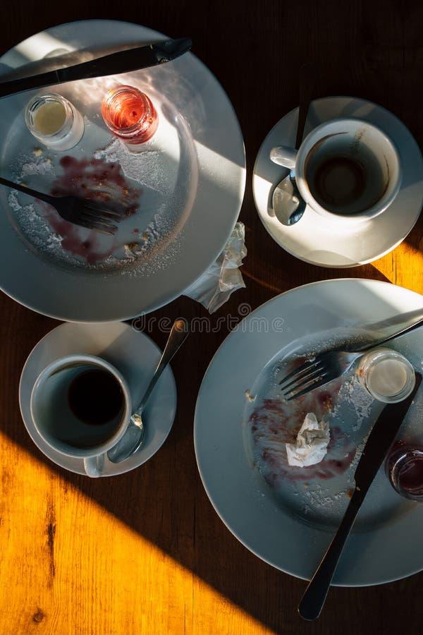 Hoogste menings vuile schotels na cake en koffie voor twee De spontane koffie van de fotolijst met resten van lunch, verfrommelde stock foto