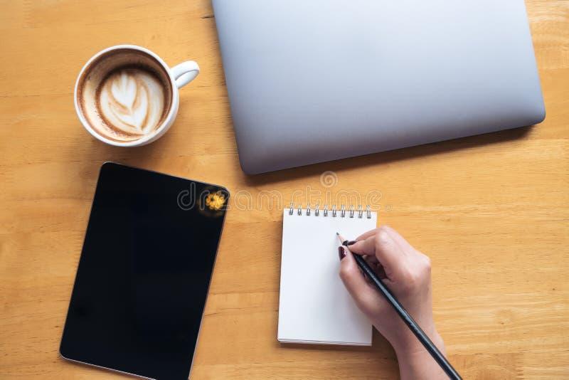 Hoogste meningsbeeld van een de holdingspotlood van de vrouwen` s hand aan het schrijven op leeg notitieboekje met tablet, laptop royalty-vrije stock afbeelding