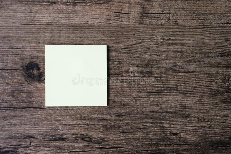 Hoogste meningsbeeld van leeg kleverig notadocument op de houten lijst stock afbeelding