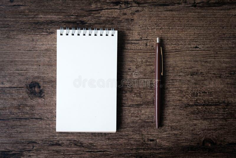 Hoogste meningsbeeld van open notitieboekje met blanco pagina en pen op w stock fotografie