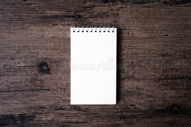 Hoogste meningsbeeld van open notitieboekje met blanco pagina op houten Ta stock afbeeldingen