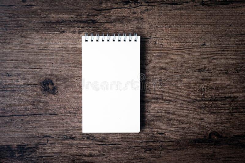 Hoogste meningsbeeld van open notitieboekje met blanco pagina op houten Ta stock foto
