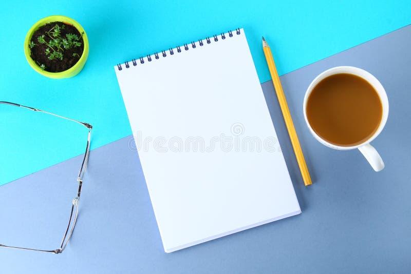 Hoogste meningsbeeld van open notitieboekje met blanco pagina's en koffie op blauwe achtergrond, klaar voor het kloppen of spot S stock afbeeldingen