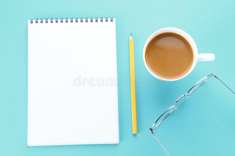 Hoogste meningsbeeld van open notitieboekje met blanco pagina's en koffie op blauwe achtergrond, klaar voor het kloppen of spot S stock fotografie