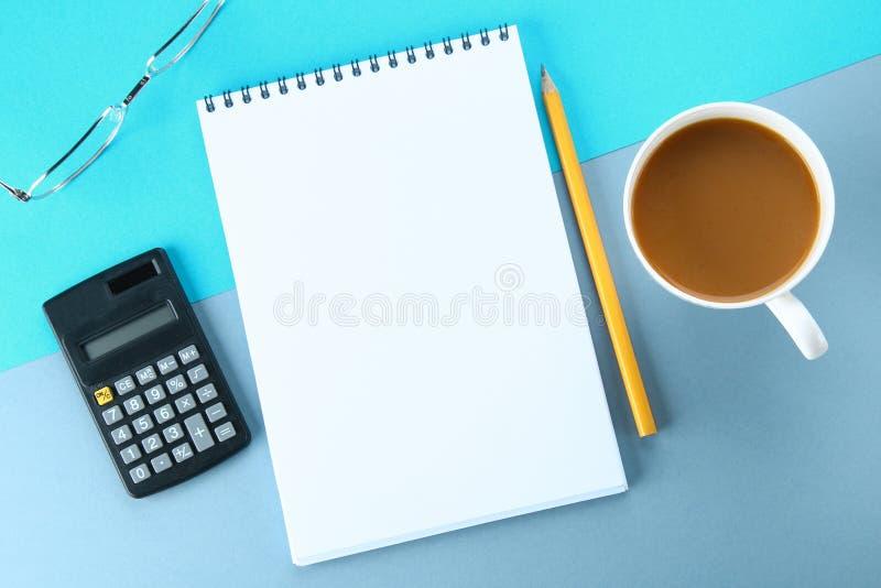 Hoogste meningsbeeld van open notitieboekje met blanco pagina's en koffie op blauwe achtergrond, klaar voor het kloppen of spot S stock foto's