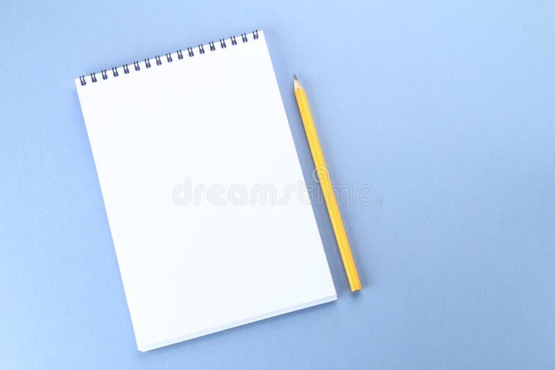 Hoogste meningsbeeld van open notitieboekje met blanco pagina's en koffie op blauwe achtergrond, klaar voor het kloppen of spot S stock afbeelding