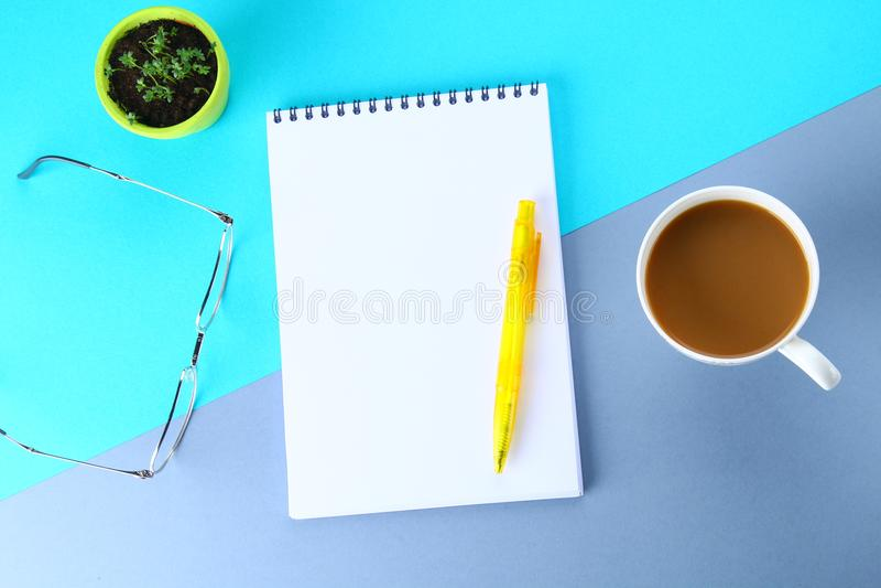 Hoogste meningsbeeld van open notitieboekje met blanco pagina's en koffie op blauwe achtergrond, klaar voor het kloppen of spot S royalty-vrije stock afbeelding