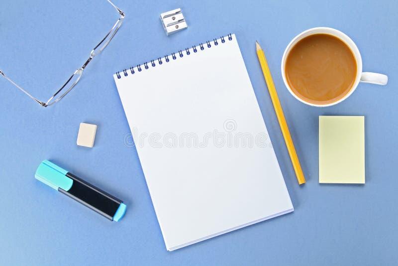 Hoogste meningsbeeld van open notitieboekje met blanco pagina's en koffie op blauwe achtergrond, klaar voor het kloppen of spot S stock foto
