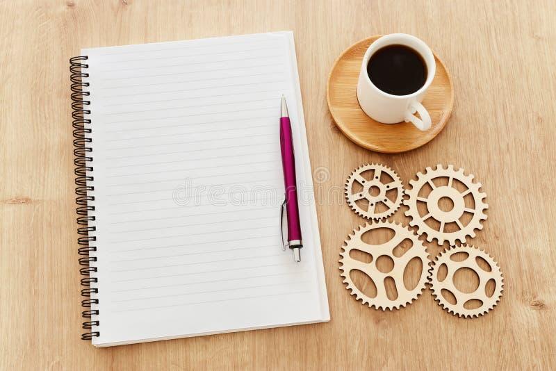 hoogste meningsbeeld van open notitieboekje met blanco pagina's naast kop van koffie op houten lijst klaar voor het toevoegen van stock foto