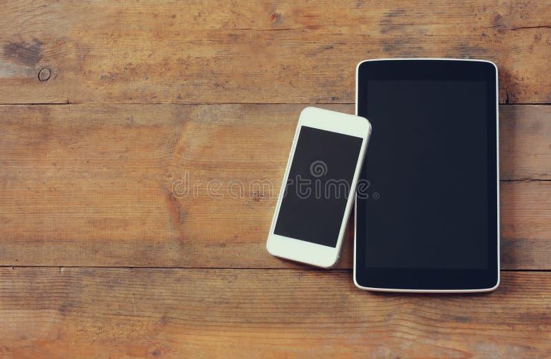 Hoogste meningsbeeld van smartphone en tabletapparaat over houten lijstruimte voor tekst, klaar voor model royalty-vrije stock afbeeldingen
