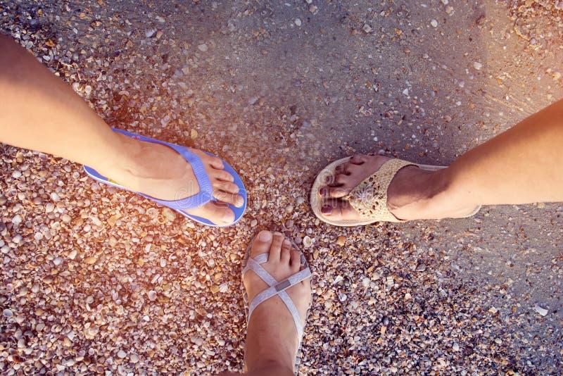 Hoogste meningsbeeld van vier verschillend paar pantoffels die van Aziatische vrouw zich in een cirkel bij het zandige strand bev royalty-vrije stock foto