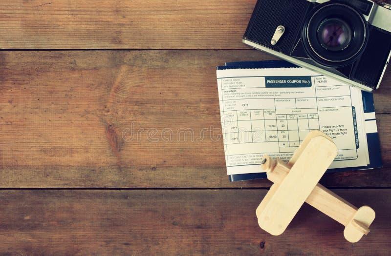 Hoogste meningsbeeld van vliegend kaartjes houten vliegtuig en uitstekende camera over houten lijst stock afbeeldingen