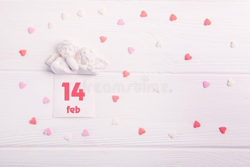 Hoogste meningsbeeldje van twee kleine mooie engelen met kaart met 14 februari-datum op de witte houten achtergrond met veelkleur stock foto's