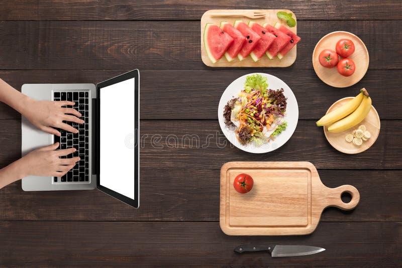 Hoogste meningsconcept met het gebruiken van laptop, verse groenten en vruchten stock foto's