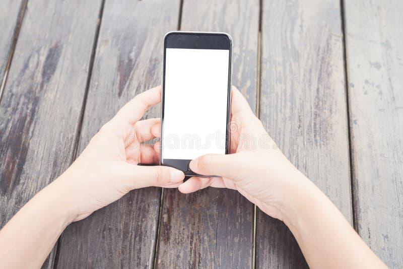 Hoogste meningshand die het smartphone witte scherm op houten lijst met behulp van royalty-vrije stock fotografie