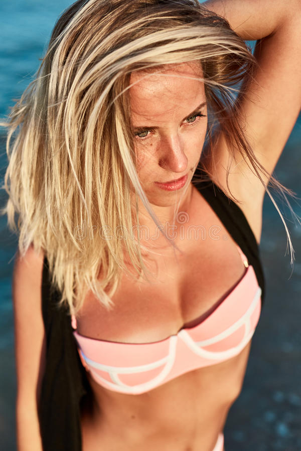 Hoogste meningsportret van jonge vrouw in een zwempak op het strand royalty-vrije stock afbeelding
