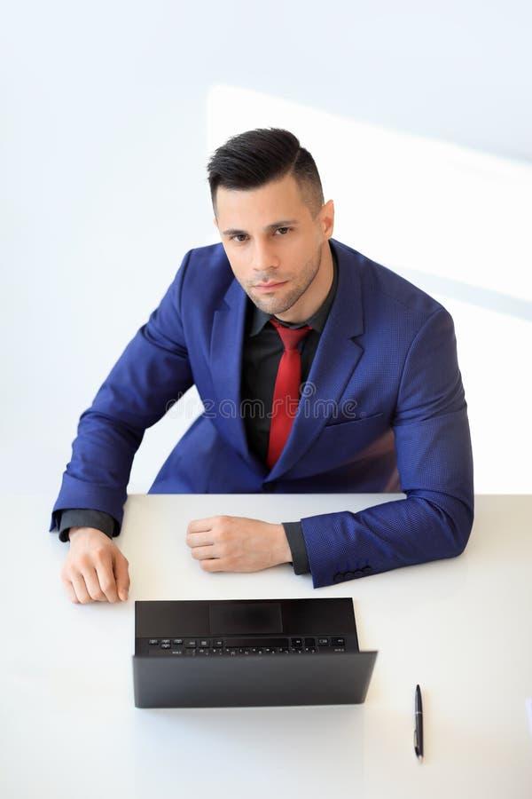 Hoogste meningsportret van jonge zekere zakenmanzitting bij zijn bureau stock foto