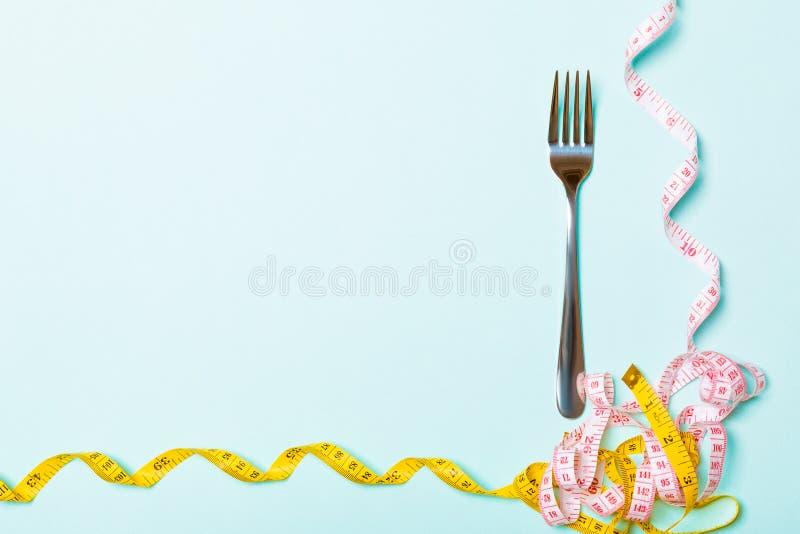 Hoogste meningssamenstelling van vork en gekruld metend band op blauwe achtergrond met lege ruimte voor uw ideeën overgewicht en stock afbeelding