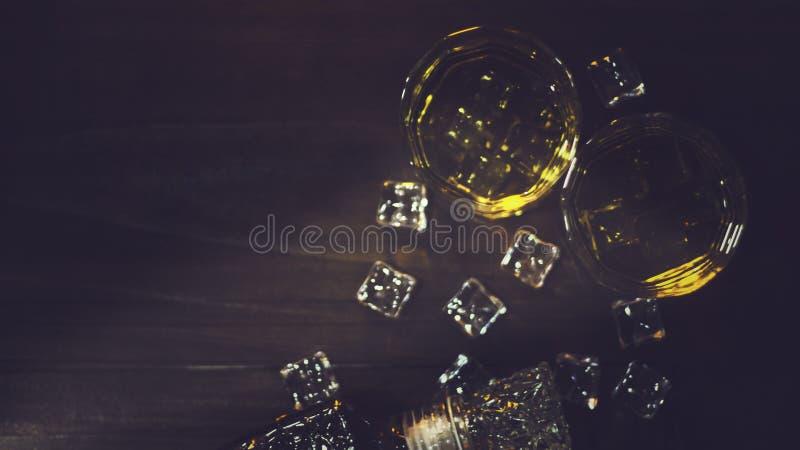 Hoogste meningswhisky in glas met mooi amberdieijs, op houten lijst met ruwe oppervlakte tegen donkere achtergrond wordt geplaats stock foto