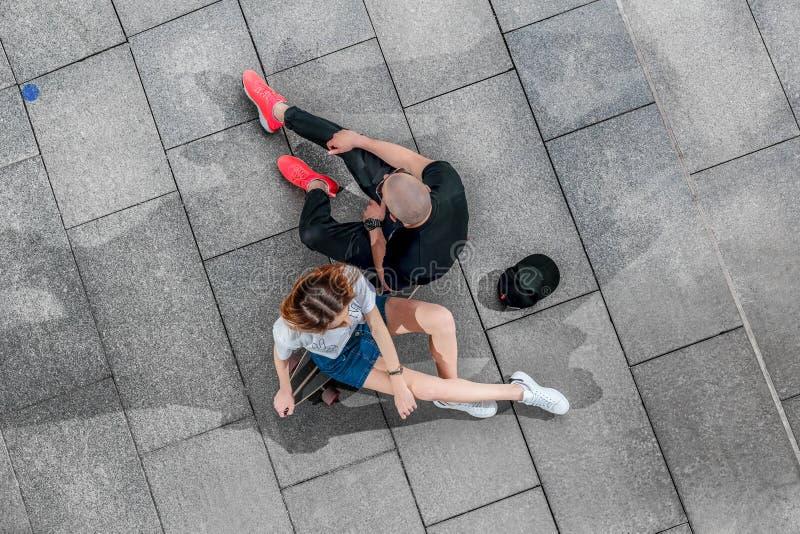 Hoogste van de meningsman en vrouw zitting op een longboard stock afbeeldingen