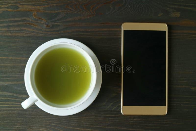 Hoogste Weergeven van de Hete Groene Thee van Matcha met het Leeg Scherm Smartphone op Donkere Bruine Houten Lijst stock afbeelding