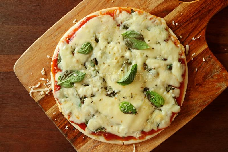 Hoogste Weergeven van Pizza met de Kaas, de Tomatensaus en Basil Served van Halloumi op Houten Plaat stock foto