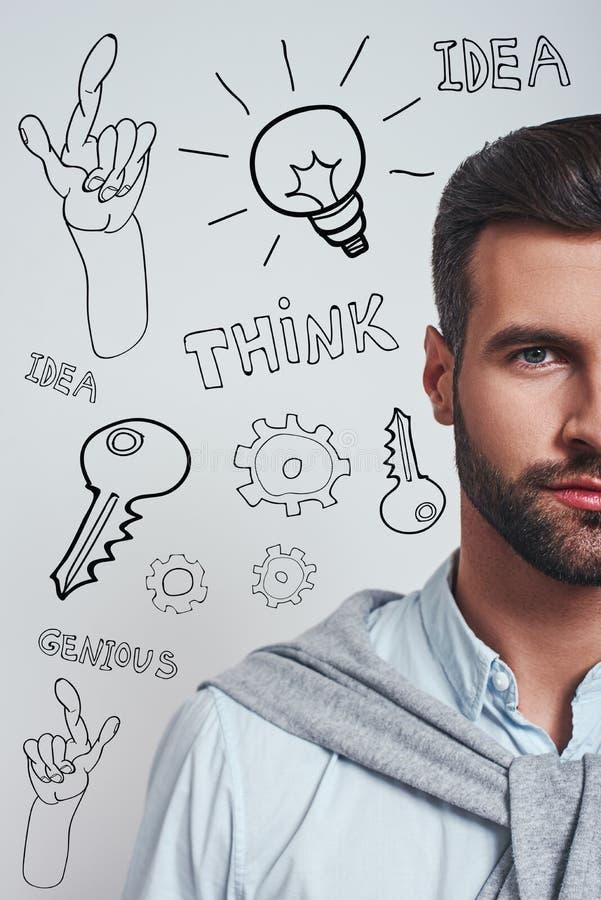 Hoogtepunt van ideeën Verticaal half gezichtsportret van een zekere gebaarde mens die in blauw overhemd camera bekijken terwijl s stock foto