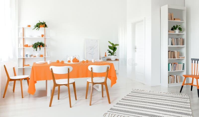 Hoogtepunt van lichte eetkamer met wit murenvloer en meubilair Plank met partij van boeken en installatie in de hoek royalty-vrije stock afbeelding
